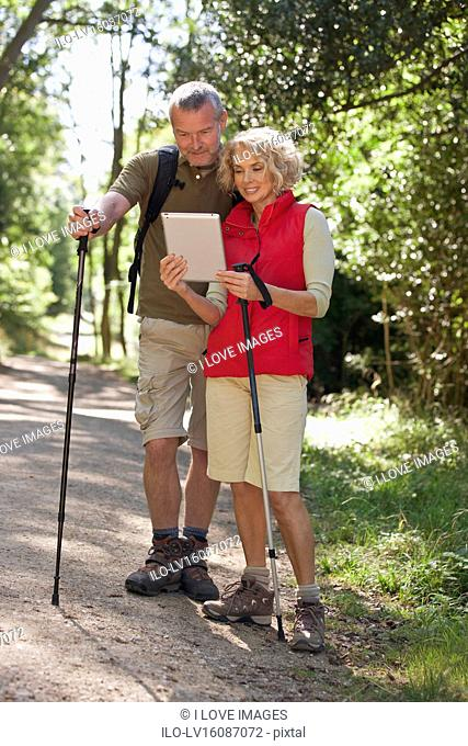 A mature couple out walking on a country path, navigating with a tablet computer