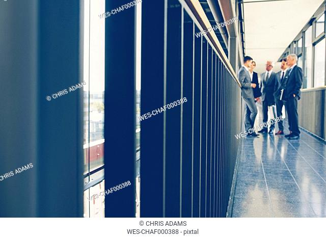 Group of business people standing on office corridor