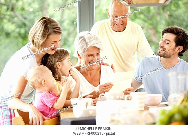 Happy granddaughter with her family reading letter at breakfast table