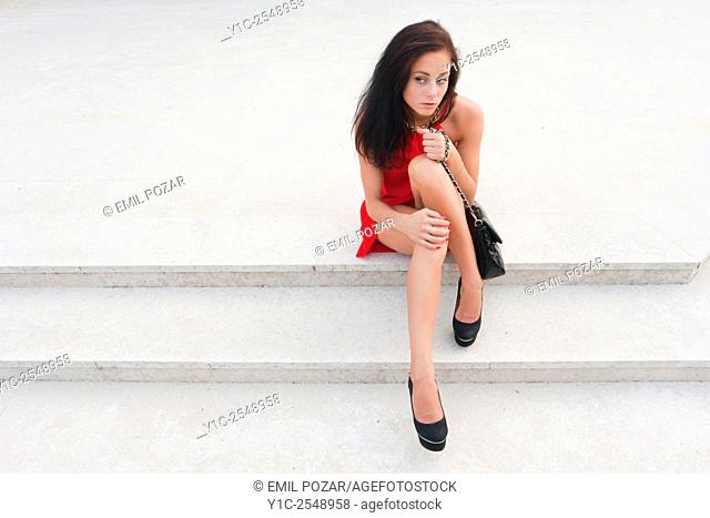 Female teen in Red dress sitting low on steps