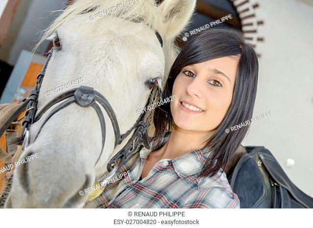 Beautiful young brunette girl and white horse