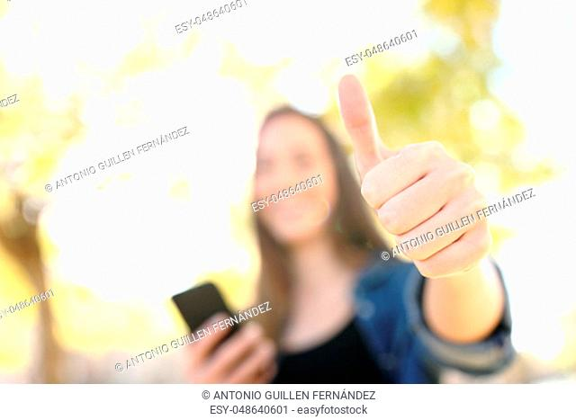 Happy woman holding smart phone with thumbs up in a park