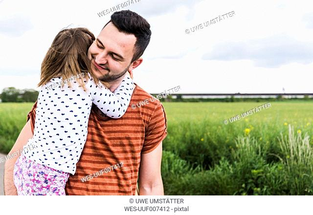 Daughter hugging father outdoors