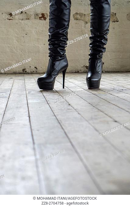 Woman wearing high leather boots indoors