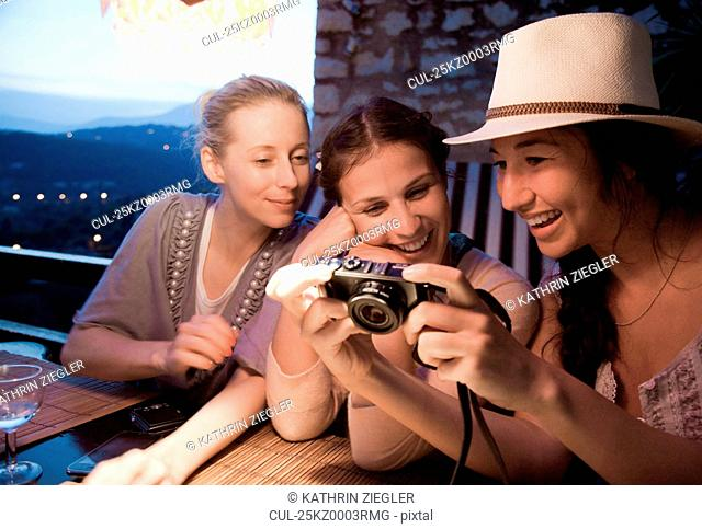 Three women looking at digital pictures