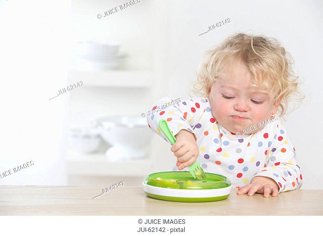 Determined baby eating avocado with fork