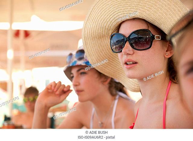 Row of teenage girls wearing sunhats relaxing under beach umbrellas