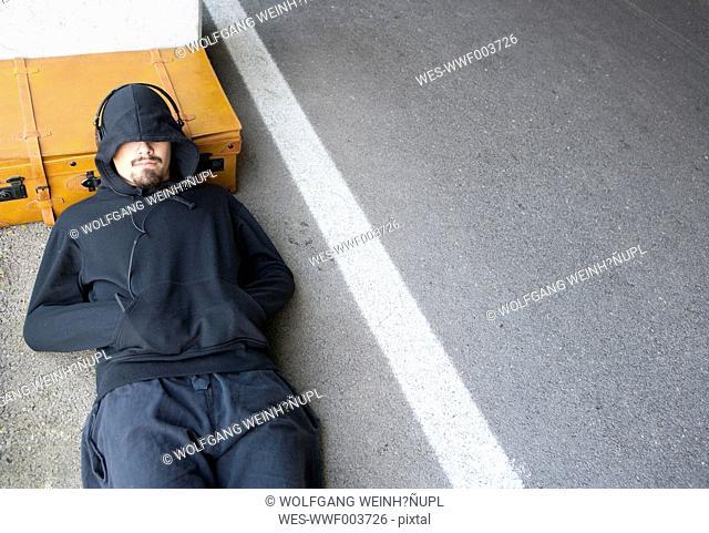 Man wearing hooded jacket sleeping beside lane