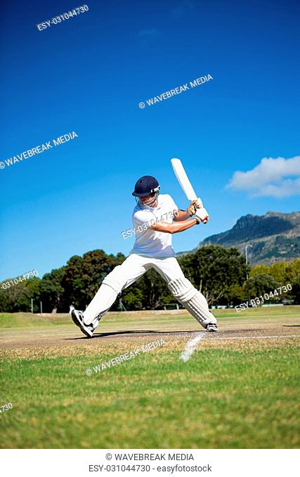 Full length of batsman playing at field against sky