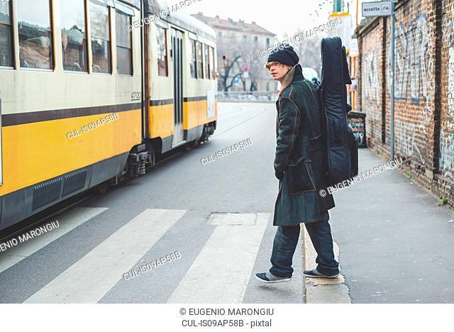 Musician crossing next to tram, Milan, Italy
