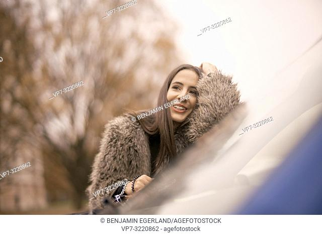 portrait of woman leaning on car window in city, Munich, Germany