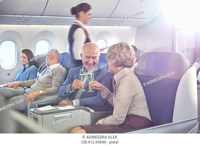Mature couple toasting champagne glasses in first class on airplane