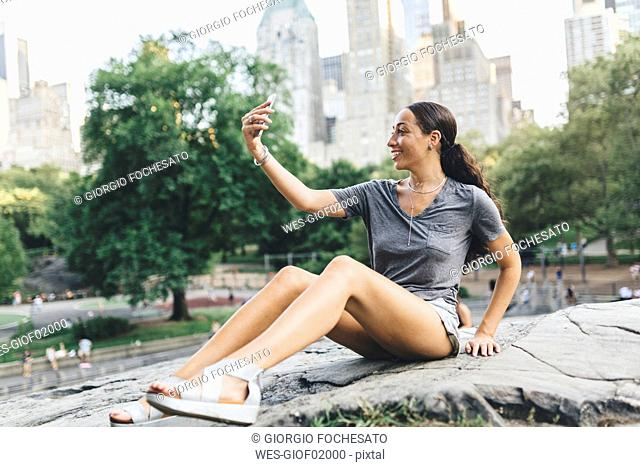 USA, Manhattan, smiling young woman taking selfie with smartphone in Central Park