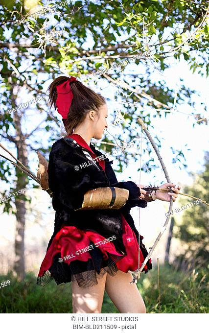 Caucasian girl in costume with bow and arrow