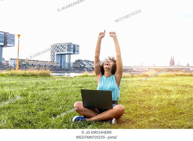Germany, Cologne, cheering woman sitting on a meadow using laptop