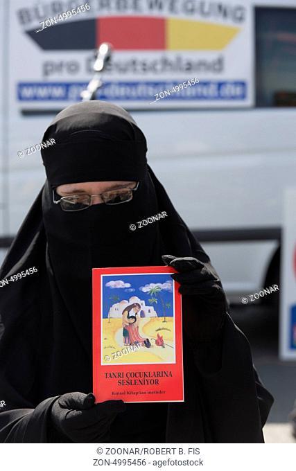 Wahlkampfauftritt der Bürgerbewegung Pro Deutschland in Bielefeld: Frau in Burka mit türkischer Kinderbibel, Foto: Robert B. Fishman, ecomedia, 26.8