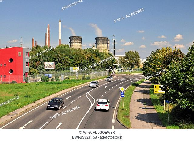 road traffic in front of the vent stacks and burners of an oil refinery, Germany, North Rhine-Westphalia, Godorf bei Wesseling