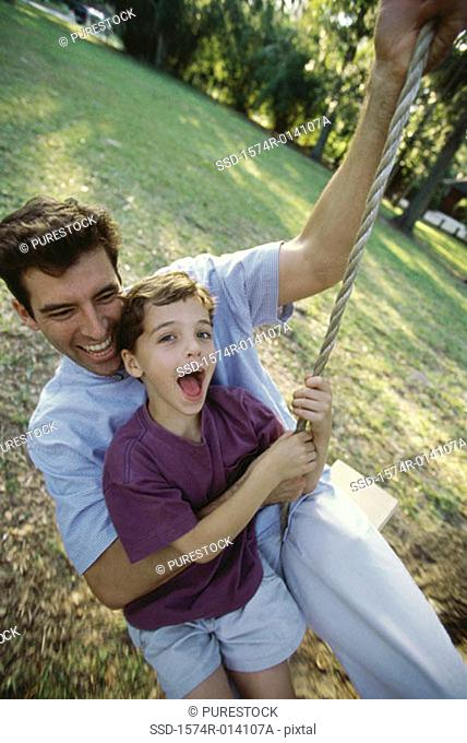 High angle view of a father and son swinging on a rope swing