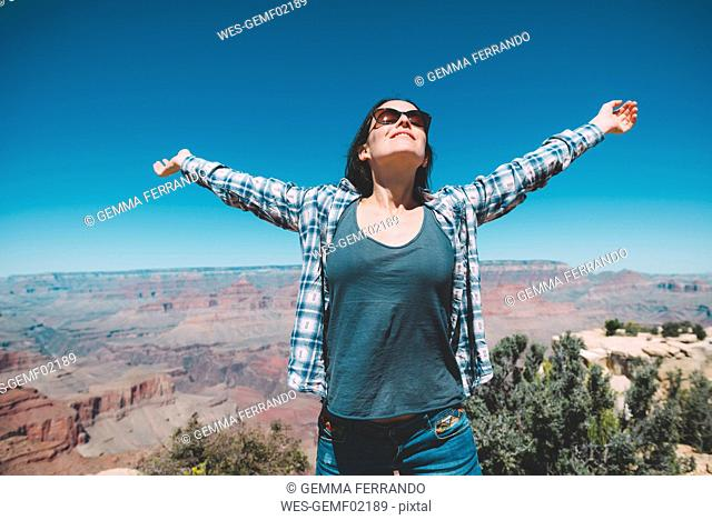 USA, Arizona, Grand Canyon National Park, happy woman in front of Grand Canyon