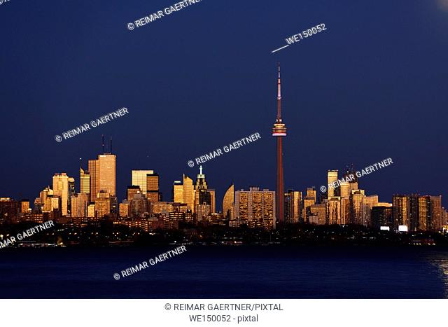 Red glow on Toronto cityscape at dusk after super moonrise
