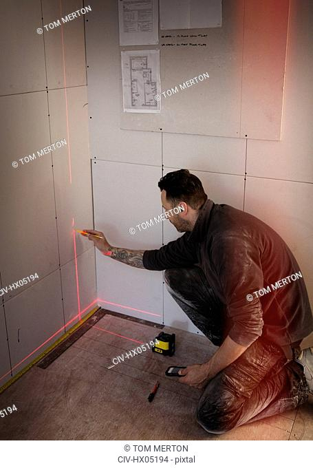 Construction worker using laser measuring tool