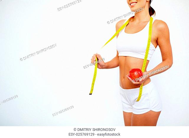 Slender girl with apple and measuring tape standing in isolation