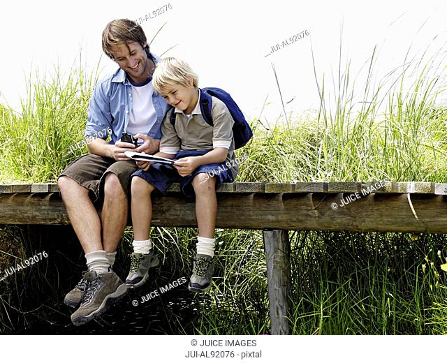 Father and son sitting on wooden footbridge