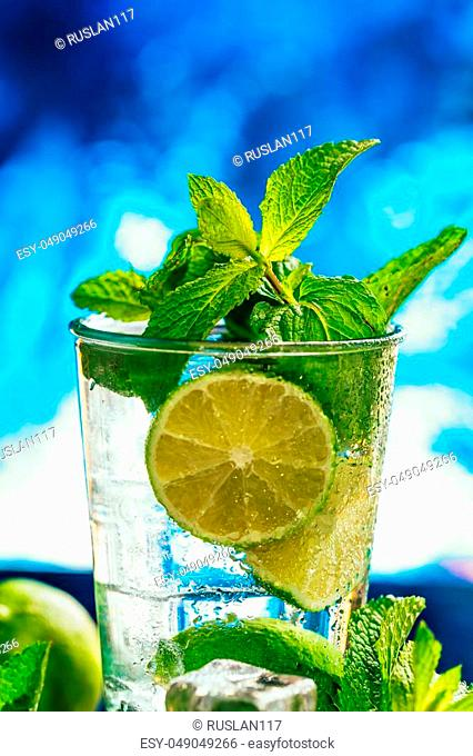 glass of mojito with lime and mint ice cube close-up with red straw on blue background