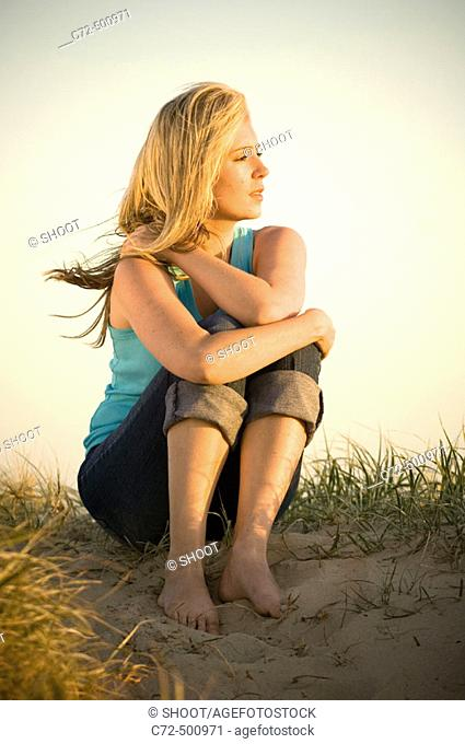 pensive woman sitting on sand