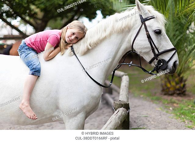 Smiling girl riding horse in yard