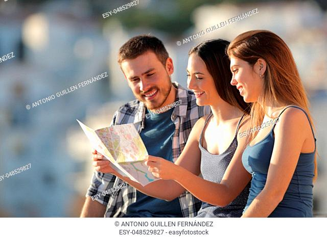 Three happy tourists checking paper map in a town on vacation at sunset