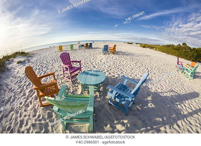 Colorful tables and chairs on the beach on a sunny day at the South Beach Bar & Grill on Gasparilla Island Florida