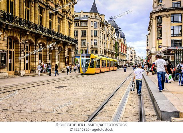 Yellow city trams on Rue des Vasle in reims France