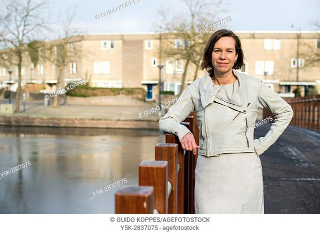The Hague, Netherlands. Portrait of a caucasian woman leaning on a park bridge railing