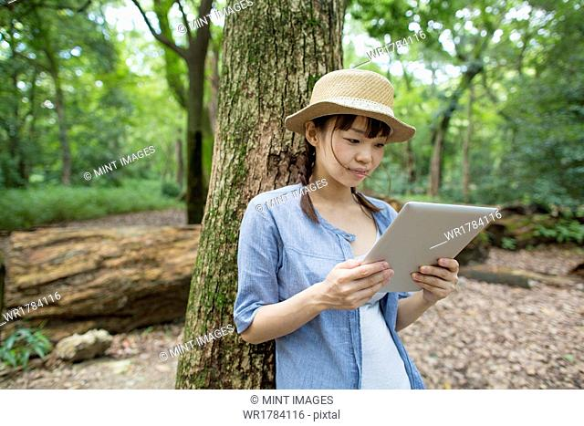 Young woman holding a digital tablet in a forest