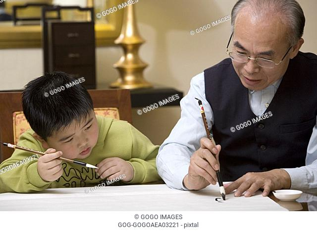 Middle-aged man teaching calligraphy to grandson