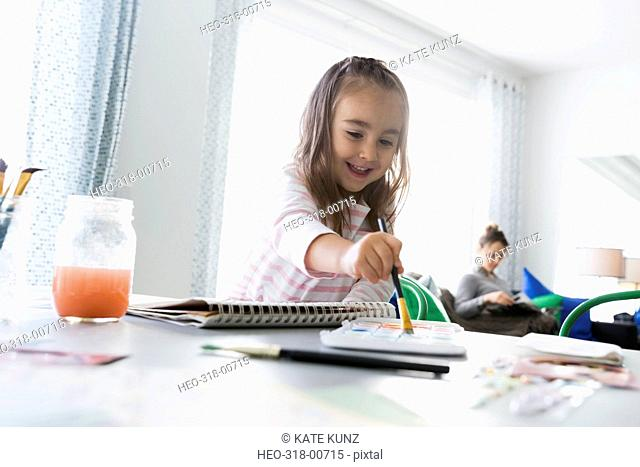 Smiling girl painting at dining room table with mother in background