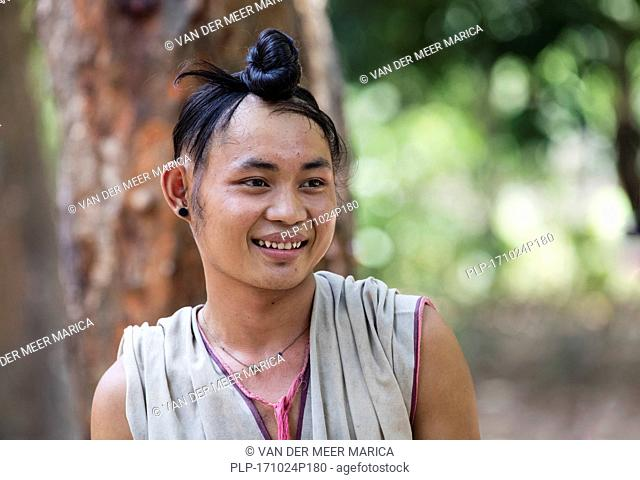 Close up portrait of young Bamar man with long hair tied in a knot in Kayin village near the town of Hpa-an, Kayin State / Karen State, Myanmar / Burma