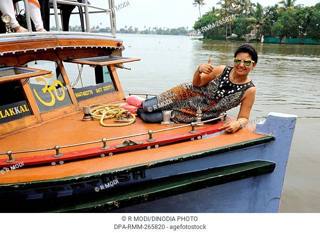woman lying on deck of boat backwater, Munnar, Kerala, India, Asia, MR#802B
