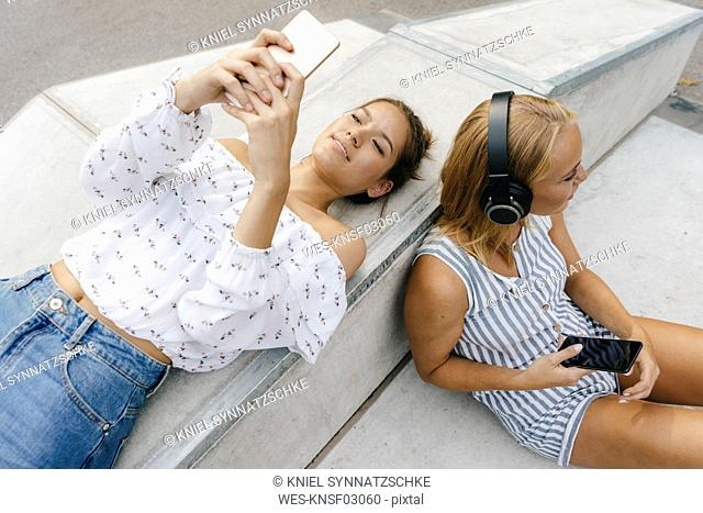 Two young women with cell phones and headphones in a skatepark