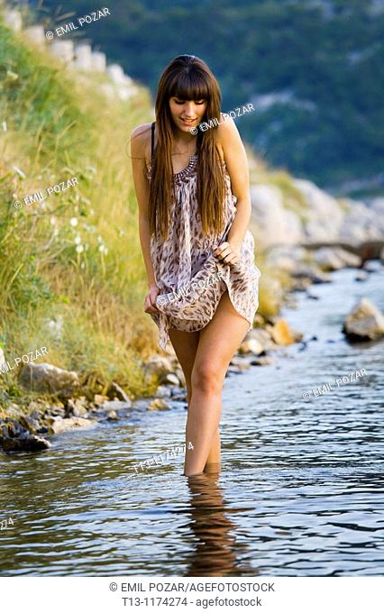 Pretty young woman is walking on the coastline