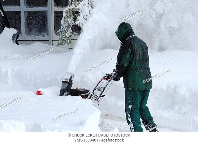 Man using snow blower to clear a driveway after a blizzard