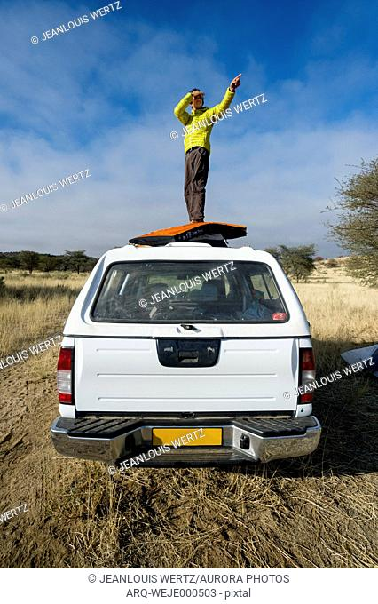 A man searching for new boulders. Bouldering expedition to Namibia