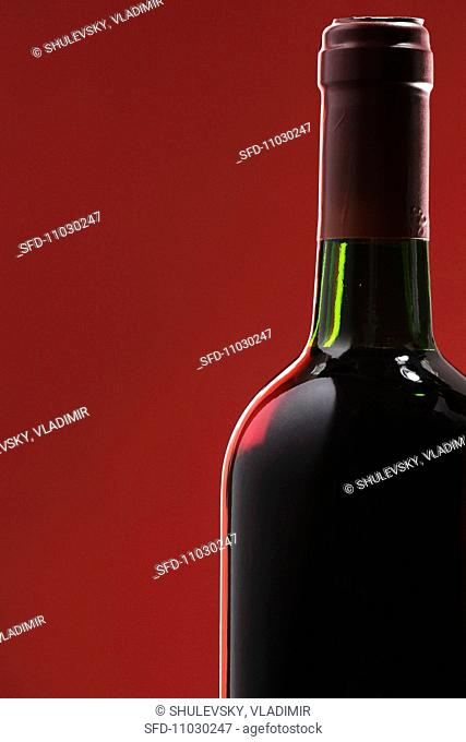 Bottle of red wine against a red background
