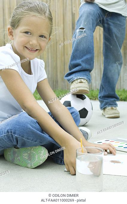 Girl sitting on driveway, painting, boy with foot on soccerball in background