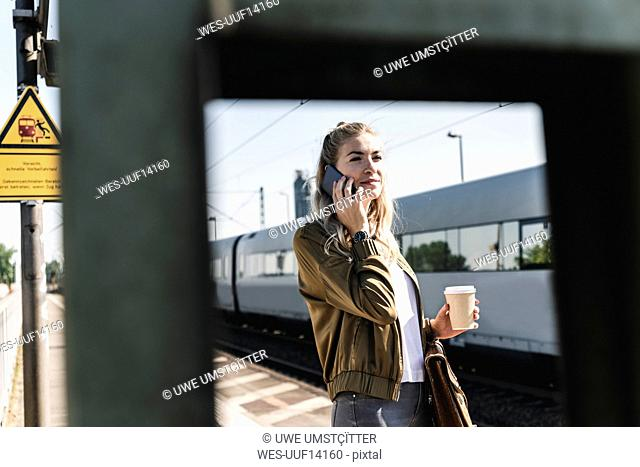 Young woman at train station talking at the phone