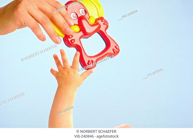 close-up, hand of baby gribs after a plasic toy in the hand of the mother  - GERMANY, 27/04/2003