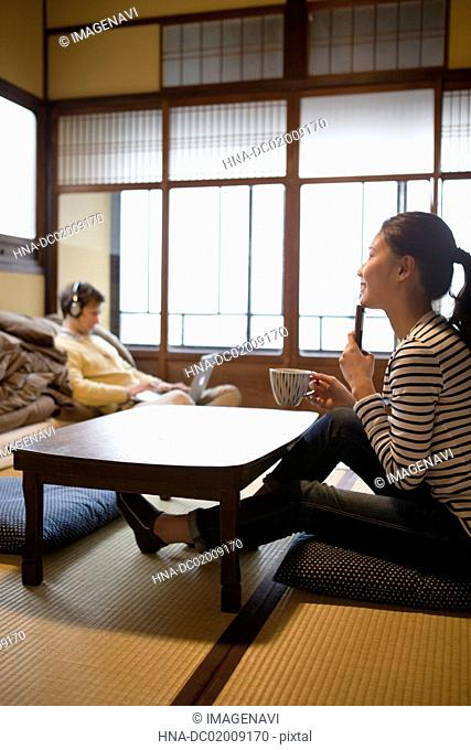 Young Japanese woman using smartphone and Caucasian man using laptop