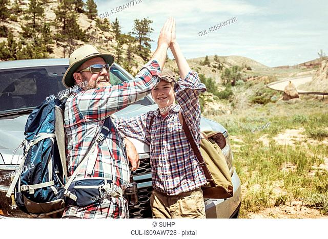 Man and teenage son on hiking road trip high fiving each other in landscape, Bridger, Montana, USA