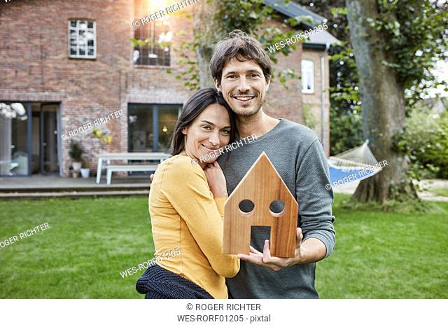 Portrait of smiling couple in garden of their home holding house model